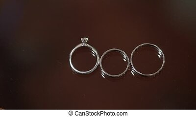 Three wedding rings on brown background