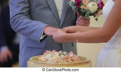 Bride puts on wedding ring on groom's hand