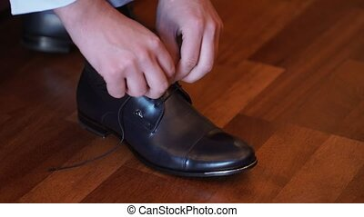 Man wearing shoes, tie the laces closeup