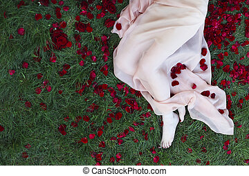 Close up shot of beautiful woman feet with red pedicure and red roses aroun
