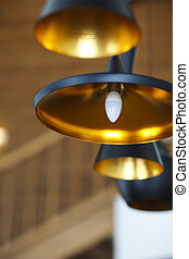 Black pendant lamp on ceiling wood wall. Close up