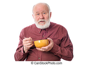Senior man eating from oragne bowl , isolated on white -...