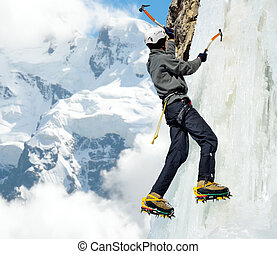 Man climbing on icefall in winter mountains