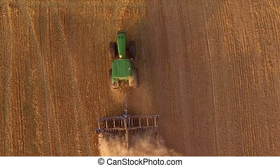 Field, tractor and dust. Agricultural machine with plow.