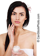 Woman with cream - Beautiful woman rubs cream face, isolated...
