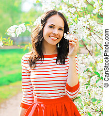 Portrait happy smiling woman at spring flowers garden