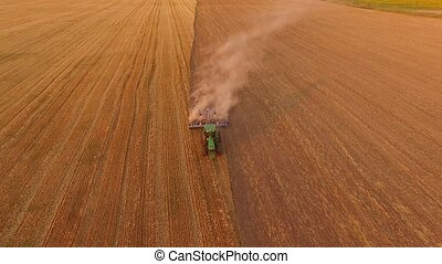 Aerial view of moving tractor. Machine with plow raising...