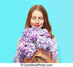 Happy smiling woman enjoying smell of bouquet lilac flowers...