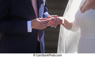 Groom wearing wedding ring on bride's hand on ceremony