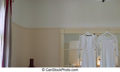 Two wedding dresses in room shot