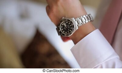 Man puts on wrist watches closeup