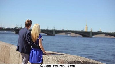 Young lovely couple embracing on embankment