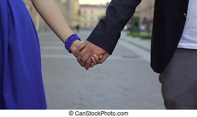 Young lovely couple holding hands and walking in a city