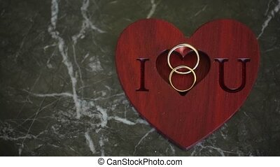 Two wedding rings and i love you sign on green marble...
