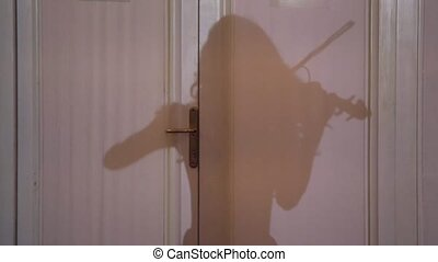 Woman playing violin shadow on wall