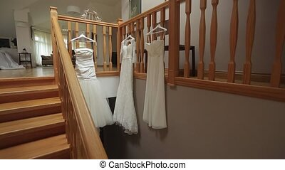 Three wedding dresses on stairs indoors