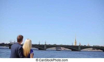 Young lovely couple embracing on embankment at sunny day