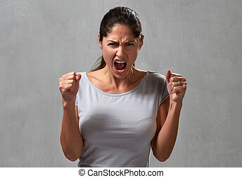 Angry woman - Angry screaming young woman over gray wall...