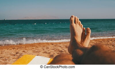Legs of Man Lying on Beach Sun Lounger near the Sea. Man lie...