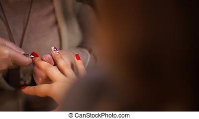 Female hands manicure close up view. Cutting burrs.