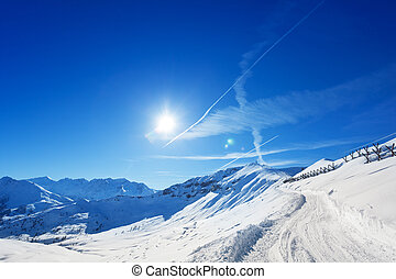 Snowcapped alpine path with anti avalanche barrier -...