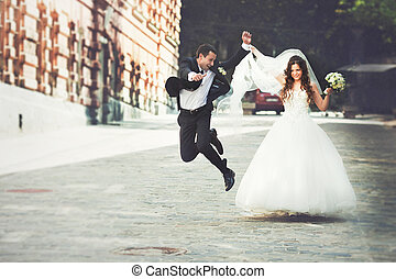 Happy groom jumps walking down the street with a bride