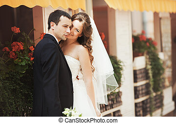 Groom looks far away holding a smiling bride in his hands
