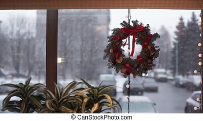 Christmas wreath of fir branches on swindow at snowly day