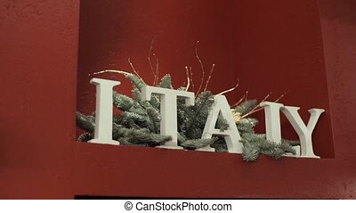 Italy sign and christmas fir decoration indoors