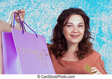 Happy smiling woman holding colourful shopping paper bags, credit card