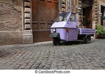 Rome, Italy. Cobblestone street and a funny three wheeled...