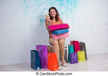 Happy woman after shopping with colourful bags, boxes, banking card
