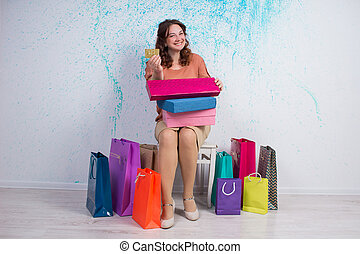 Happy woman after shopping with colourful bags, boxes, credit card