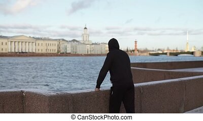 Unrecognizable man staying on city embankment at winter...