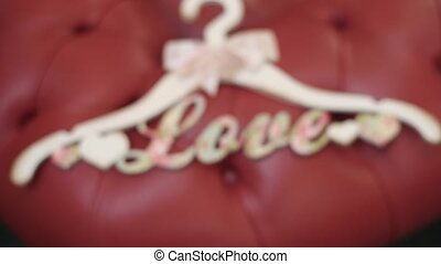 Hanger for clothes with love word on red chair