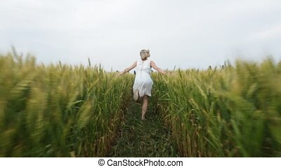 Woman with blonde hair in a blue dress runs in the field...
