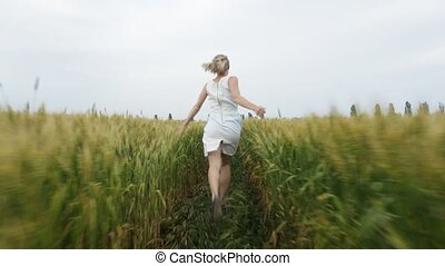 Woman with blonde hair in a blue dress runs in the field with wheat.