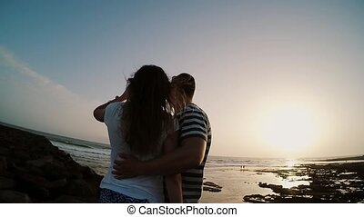 Man and woman standing on the shore by the sea, hugging and watching on sunset. Couple on evening beach. Slow motions.