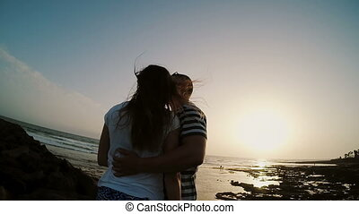 Man and woman standing on the shore by the sea, hugging and kissing on the sunset. Couple on sunset beach.