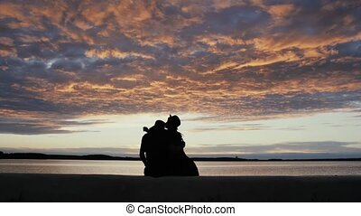 Silhouette of a stylish young couple in love sitting on the promenade by the sea beautiful sunset sky on the background