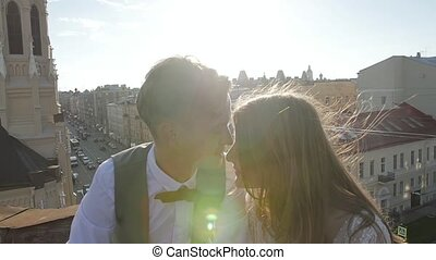 Happy young beautiful stylish couple bride and groom kiss...