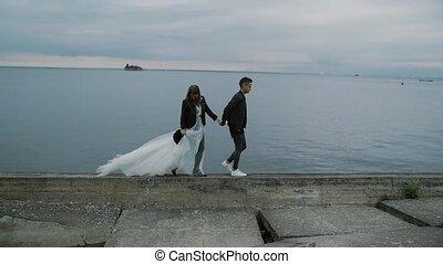 beautiful stylish couple bride and groom walking along the...