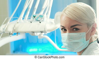 Closeup face of young woman dentist in mask on her in dental...