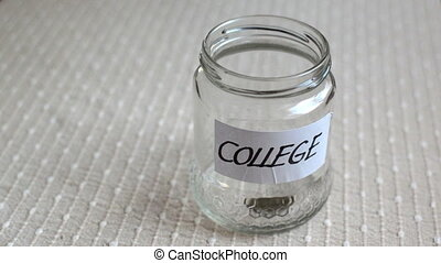Coins filling in jar labeled for college - Coins filling and...