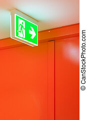 Bright green safety exit signal. Help to escape in an...