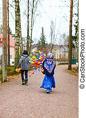Easter in Finland - Back view of kids outdoors dressed for...