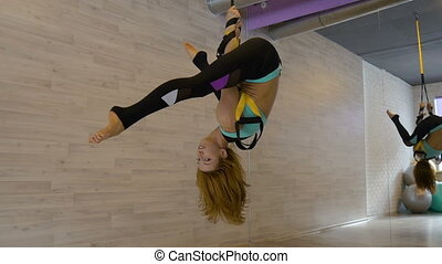 Young sexy girl doing stretching, hanging upside down in the...