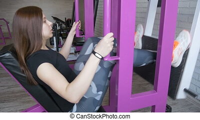 Beautiful girl is engaged on simulators. A healthy...