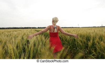 Woman with blonde hair in a red dress walking in the field with wheat.