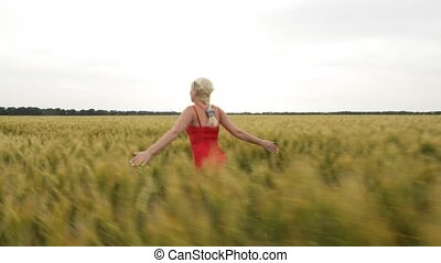 Woman with blonde hair in a red dress runs in the field with wheat.
